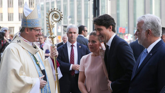 Archbishop Christian Lepine of Montreal smiles as he greets Canadian Prime Minister Justin Trudeau before the ceremonial Mass May 17 at Notre-Dame Basilica in Montreal for the city's 375th birthday